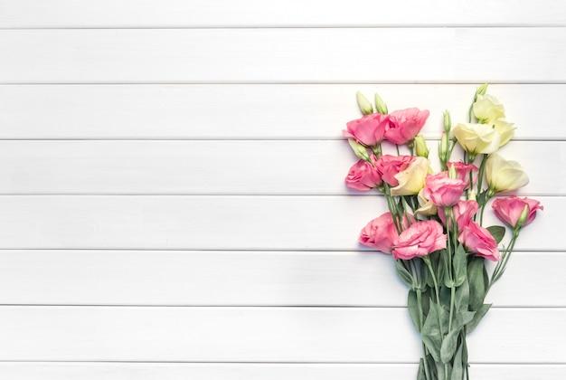 Mooie roze eustoma bloemen op witte houten achtergrond. kopieer ruimte, bovenaanzicht, Premium Foto