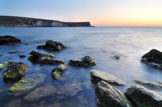 Mooie roze zonsondergang over nog steeds zeewater en waterstenen met groen mos in de krim Premium Foto