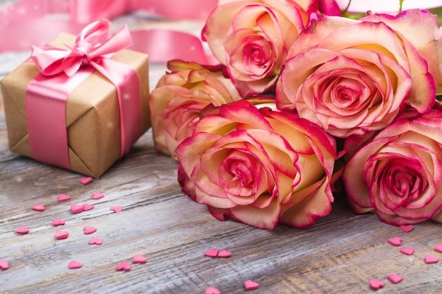 Mooie rozen en geschenkdoos op houten achtergrond. valentijnsdag of moeders dag wenskaart Premium Foto