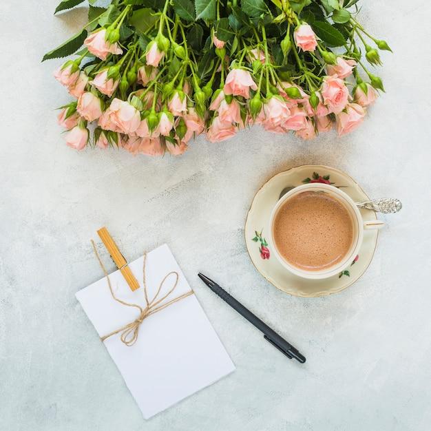 Mooie rozen; knoppen; wenskaart; pen en koffiekopje op concrete achtergrond Gratis Foto