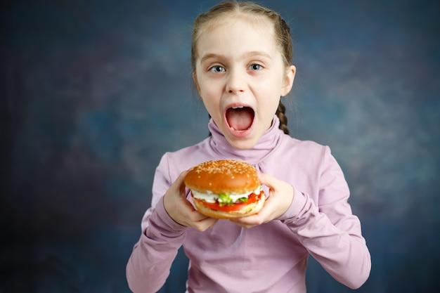 Mooie schattige kleine blanke blonde meisje met hamburger Premium Foto