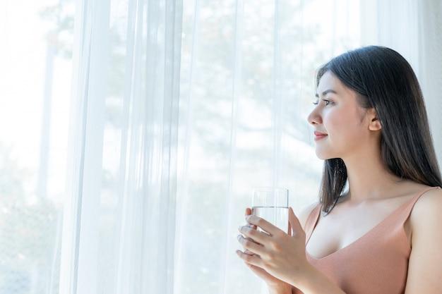 Mooie schoonheid vrouw aziatische schattig meisje voelt gelukkig drinken schoon water drinken voor een goede gezondheid in de ochtend Gratis Foto