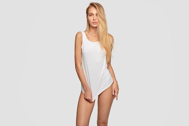 Mooie seksuele vrouw in oversized lang t-shirt met mock-up lege ruimte, heeft slanke benen, poseert tegen de muur, heeft een gezonde huid, heeft lang haar, neemt foto voor modeblad. geïsoleerde schot Gratis Foto