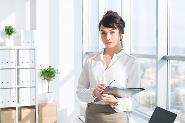 Mooie, serieuze consultant die een bril en een formeel kantoorpak draagt, haar werk stationair houdt, Premium Foto