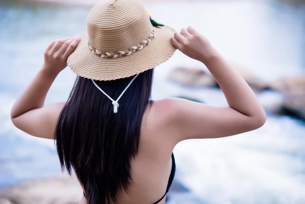 Mooie sexy jonge vrouw in bikini bij rots van waterval Gratis Foto