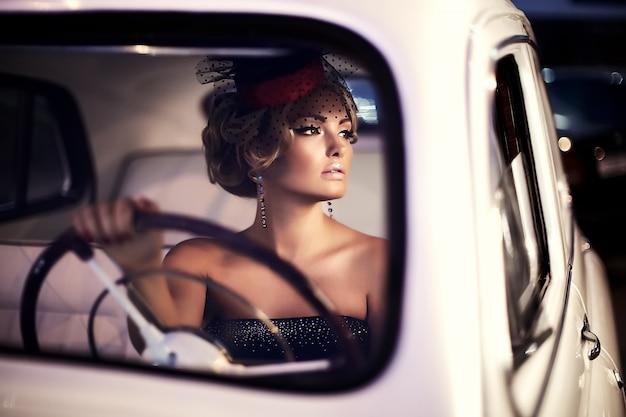 Mooie sexy mode blond meisje model met lichte make-up en krullend kapsel in retro-stijl zitten in oude auto Gratis Foto