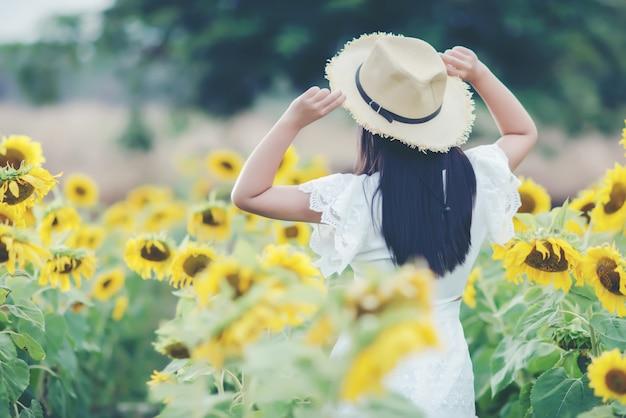 Mooie sexy vrouw in een witte jurk lopen op een veld met zonnebloemen Gratis Foto