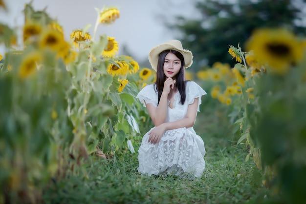 Mooie sexy vrouw in een witte jurk op een veld met zonnebloemen, gezonde levensstijl Gratis Foto