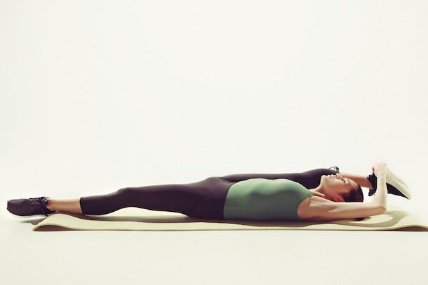 Mooie slanke brunette die wat rekoefeningen in een gymnastiek doet Gratis Foto