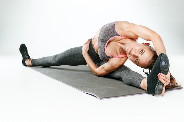 Mooie slanke brunette doet wat rekoefeningen in een sportschool Gratis Foto