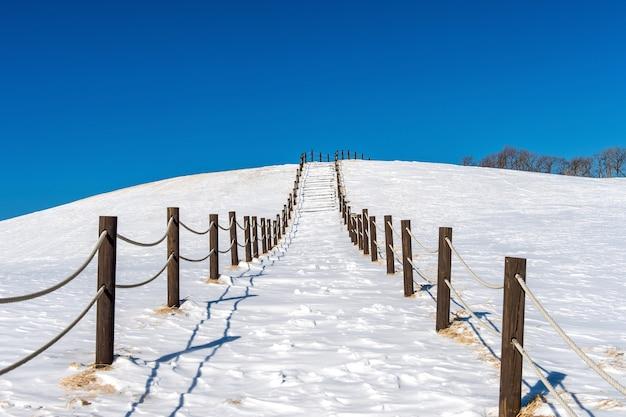 Mooie sneeuw trap loopbrug en blauwe hemel met sneeuw bedekt, winterlandschap Gratis Foto