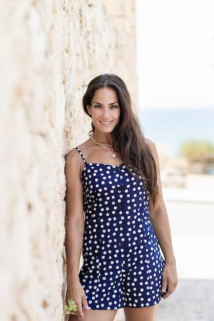 Mooie spaanse vrouw in blauwe kleding die op muur leunen terwijl het kijken camera Premium Foto