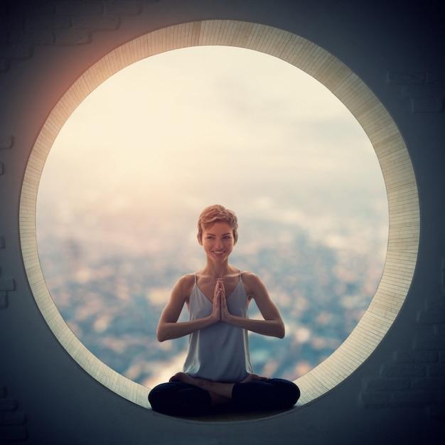 Mooie sportieve fit yogi vrouw beoefent yoga asana padmasana - lotus pose in een rond raam Premium Foto
