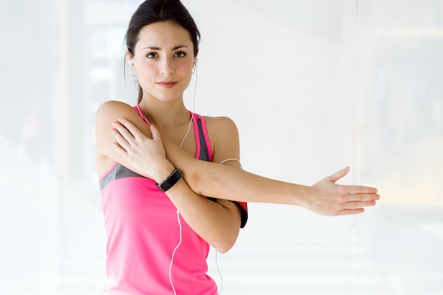 Mooie sportieve jonge vrouw die oefening in de sportschool doet. Gratis Foto