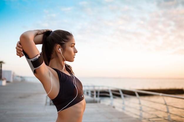Mooie sportieve meisje opleiding bij zonsopgang boven zee. Gratis Foto