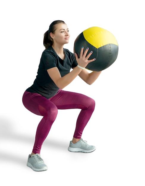 Mooie sportieve vrouw die hurkzit met med bal doet. foto van spiergeschiktheidsmodel dat op witte achtergrond wordt geïsoleerd. fitness en gezonde levensstijl concept Premium Foto