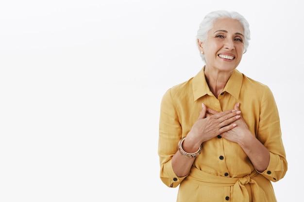 Mooie stijlvolle oudere vrouw hand in hand op hart en glimlachend opgetogen Gratis Foto