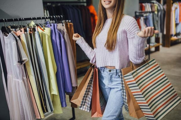 Mooie stijlvolle vrouw loopt in modern winkelcentrum Premium Foto