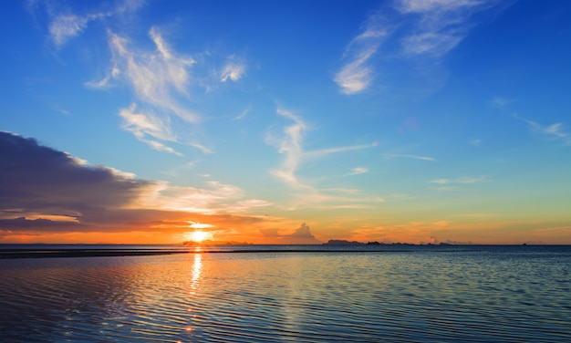 Mooie strandzonsondergang met grote regenwolken en gouden lichte hemelachtergrond Premium Foto