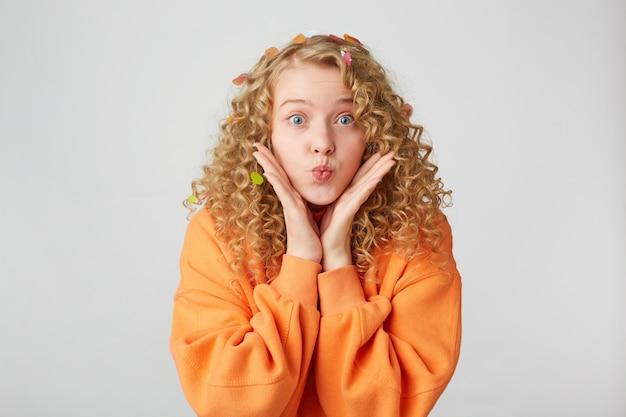 Mooie tedere aardige meid blaast luchtkus, houdt de handpalmen dicht bij het gezicht alsof ze het laat zien of probeert op te letten, gekleed in een oversized sweatshirt Gratis Foto
