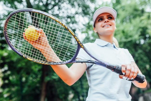 Mooie tennisspeler die bij camera op een zonnige dag met racket op haar handen glimlacht. Premium Foto