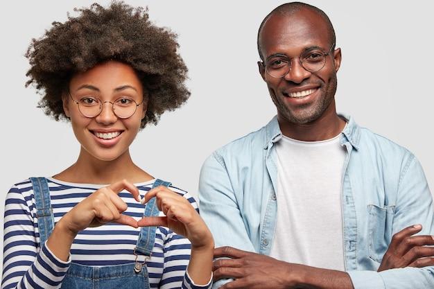 Mooie tevreden gekrulde jonge afro-amerikaanse vrouw maakt hartgebaar, drukt liefde en goede houding uit, staat naast haar vrolijke donkere vriendje, in goed humeur tijdens de date Gratis Foto