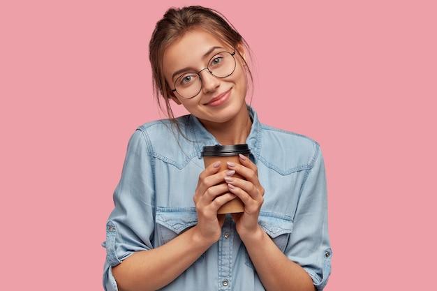 Mooie tevreden jonge blanke vrouw in ronde transparante glazen, houdt warme afhaalkoffie Gratis Foto