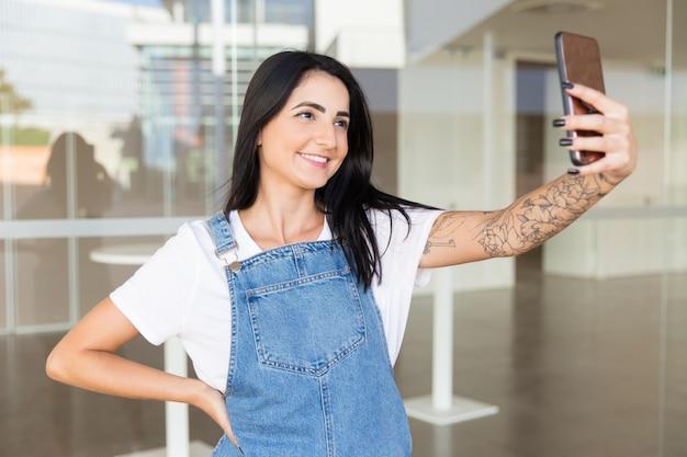 Mooie tevreden vrouw die selfie met smartphone neemt Gratis Foto