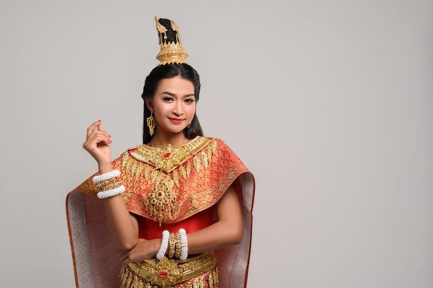 Mooie thaise vrouw die een thaise kleding en een gelukkige glimlach draagt. Gratis Foto