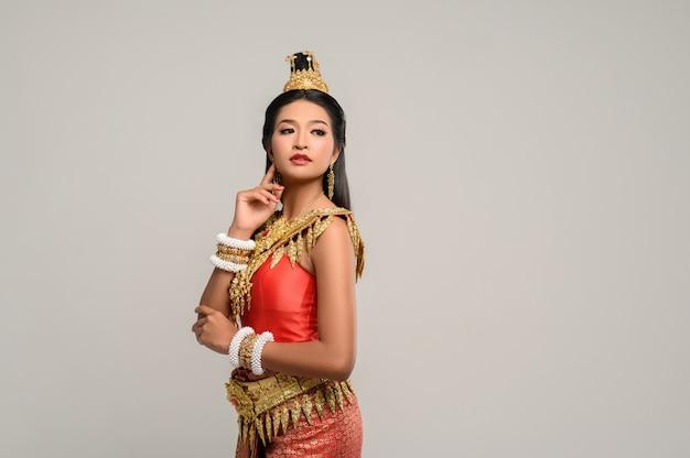 Mooie thaise vrouw die thaise kleding draagt en de bovenkant bekijkt Gratis Foto