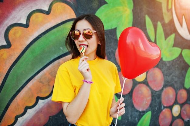 Mooie tiener die lolly met glazen, dichtbije hartballon, bij gele t-shirt likken dichtbij graffitimuur. Premium Foto