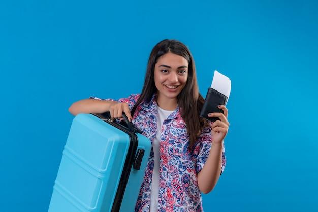 Mooie toeristische vrouw met reiskoffer en paspoort met kaartjes met glimlach op gezicht gelukkig en positief reisconcept staande over blauwe ruimte Gratis Foto