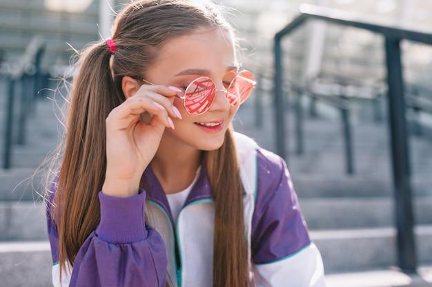 Mooie trendy jonge vrouw in stijlvolle kleding roze zonnebril dragen en glimlachen Gratis Foto