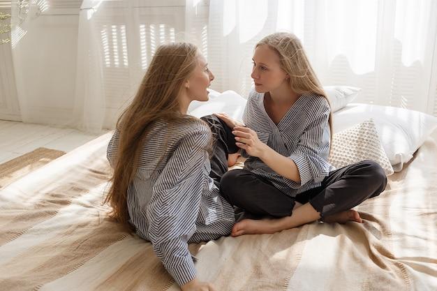 Mooie tweelingzussen in zwarte jeans, gestreepte shirts met lang haar zitten op de bank Premium Foto