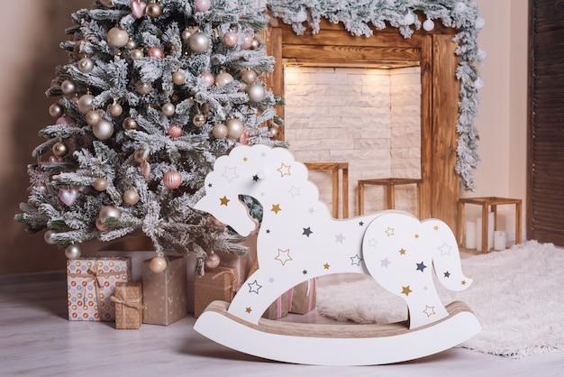 Mooie vakantie ingerichte kamer met kerstboom, houten paard en presenteert bij de open haard. Premium Foto