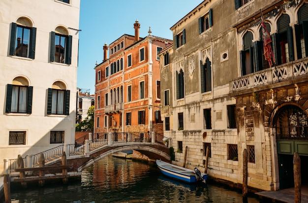 Mooie venetiaanse straat in de zomerdag, italië. venetië, prachtige romantische italiaanse stad aan zee met grote gracht en gondels, italië. Premium Foto