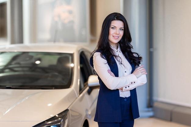 Mooie verkoopster die dichtbij nieuwe auto in dealercentrum bezit Premium Foto