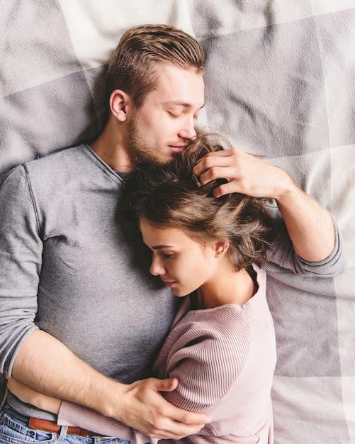 Mooie verliefde paar is luxuriating in bed samen. ze knuffelen en glimlachen Premium Foto