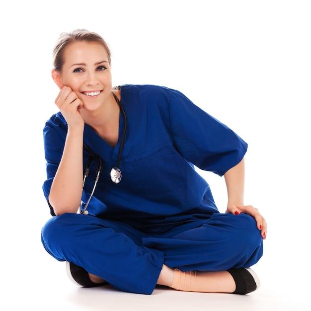 Mooie verpleegster die meditatie doet die op wit wordt geïsoleerd Premium Foto
