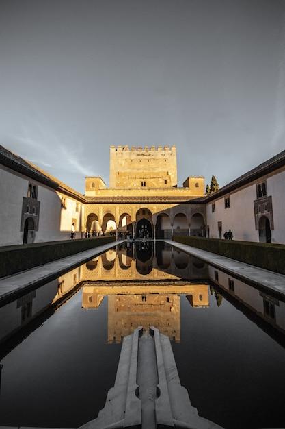 Mooie verticale opname van een groot paleis in spanje met de reflectie in het zwembad Gratis Foto