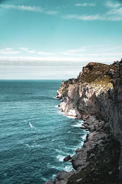Mooie verticale weergave van rotsachtige kust en de blauwe kalme zee Gratis Foto