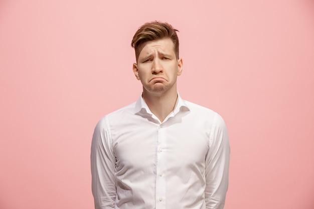 Mooie verveeld man geïsoleerd op roze muur Gratis Foto