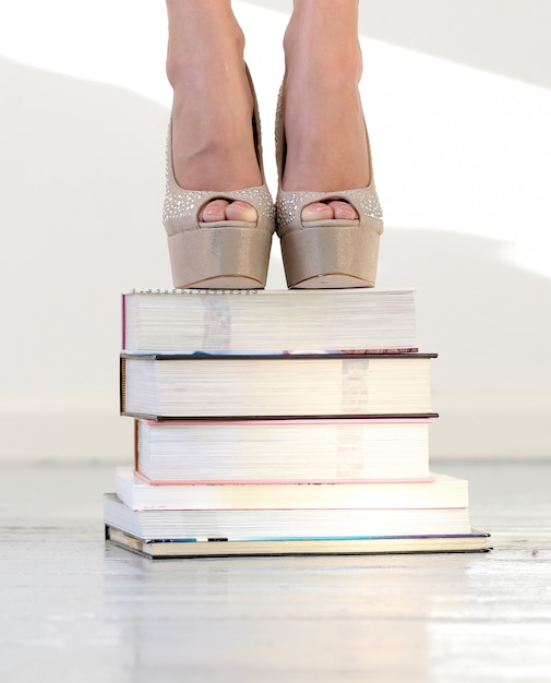 Mooie voeten op gestapelde boeken Gratis Foto