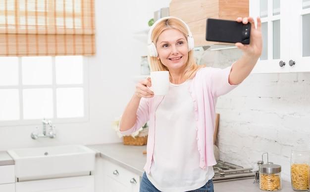 Mooie volwassen vrouw die een selfie thuis neemt Gratis Foto