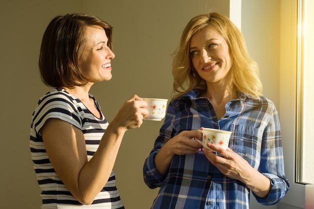 Mooie volwassen vrouw die hete koppen van koffie het drinken houdt Premium Foto