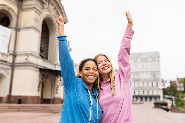 Mooie vriendinnen hand in hand in de lucht Gratis Foto