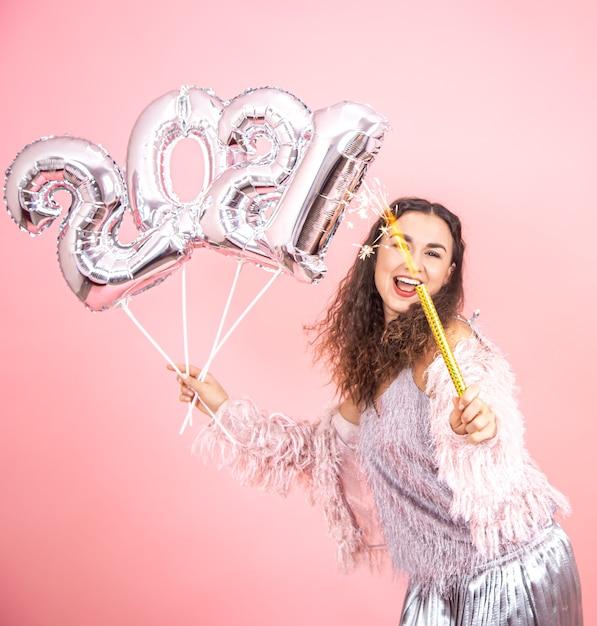 Mooie vrolijke feestelijk geklede brunette meisje met krullend haar poseren op een roze studio achtergrond met zilveren ballonnen voor het nieuwe jaar-concept Gratis Foto