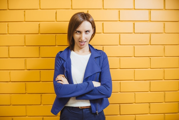 Mooie vrolijke moderne gekke vrouw op gele bakstenen muur Premium Foto