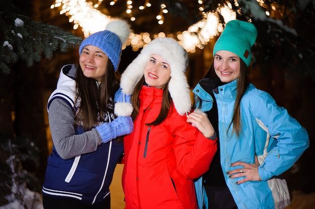 Mooie vrolijke vrouwelijke vriend in kleurrijke jasjes die pret hebben en in de stadsstraat bij nacht in kerstmistijd lopen. Premium Foto