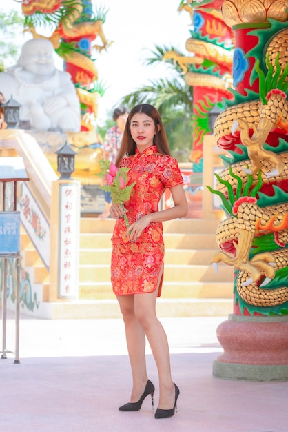 Mooie vrouw aziaat die rode kleding in chinees nieuwjaar draagt Premium Foto